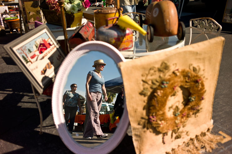 Visitors of the Rose Bowl Flea Market are reflected in a mirror displayed by a vendor at the Rose Bowl Flea Market in Pasadena, Calif., Sunday, February 13, 2011.