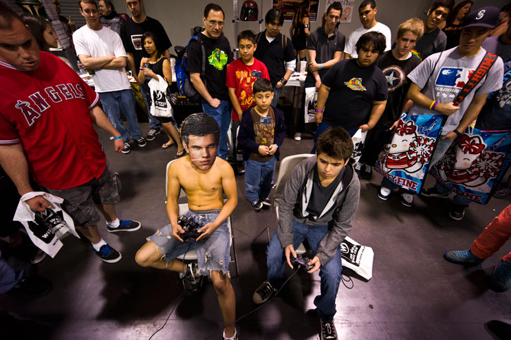 Donning a mask with Twilight character Jacob Black's face, J.R. Hipolito, center left, plays against Darren Newton during a promotion of the video game Marvel Vs. Capcom III at the 7evens Gaming stand.