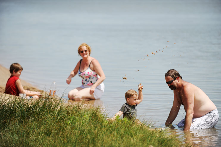 "Monica Monett, her husband Matt Reid, their son Jack Reid, 9, and their grandson Xander Doll, 1 1/2, cool off at Sloan's Lake Monday afternoon, June 13, 2011. The family moved to Denver from Lafayette, Calif., earlier this year to be near their daughter and her baby son. ""Employment was hard and everything was getting hard,"" Monett said. ""So we just packed everything that fit into our car and moved here. We love it here."""