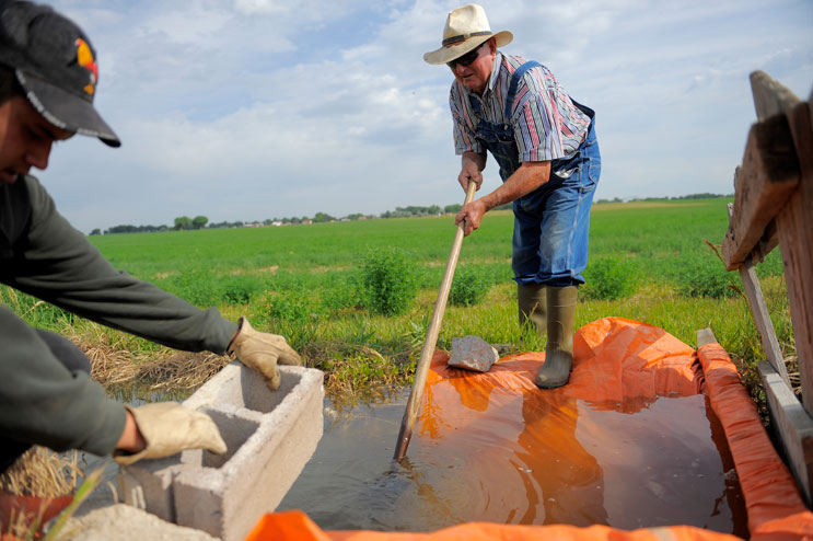"""Len Pettinger and his farmhand Salvadore Simatal set up a dam in a gravity irrigation ditch to divert water onto one of the Alfalfa hay fields on Pettinger's farm in Brighton, Colo., Thursday, June 30, 2011. """"We knew it wasn't gonna be good,"""" Pettinger said. """"Not only did we not get free water this year, but they also got double stingy about our charge water."""""""