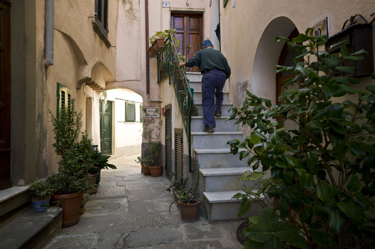 An old man climbs the stairs to his home in the mountain village of Marciana, Island of Elba, Thursday, September 22, 2011.