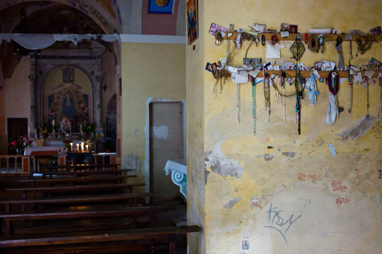 Rosaries, photographs and other offerings are lined up on a wall inside the Madonna del Monte pilgrims' church above the mountain village of Marciana, Friday, May 18, 2012.