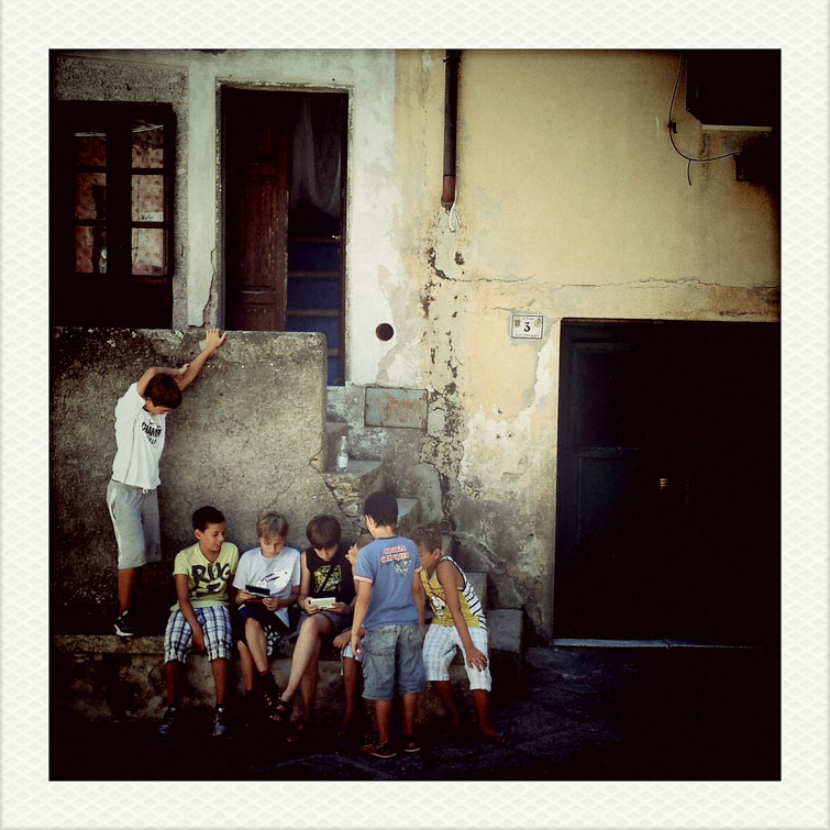 A group of local boys plays a video game in the mountain village of Marciana on the Tuscan Island of Elba, Italy, Wednseday, August 8, 2012.