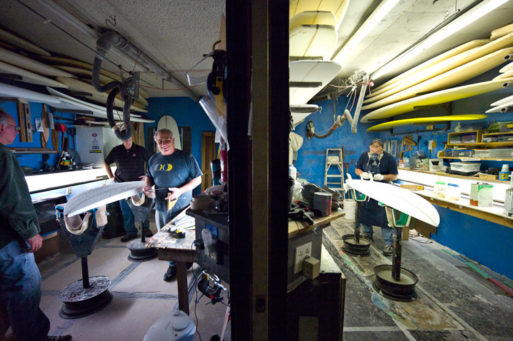 Terry Senate, center left, and Chuck Johnson, right, work in Senate's surf shop in San Clemente, Calif., Tuesday, March 15, 2011.