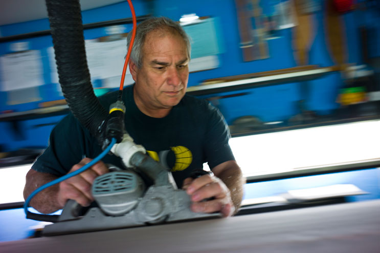 Terry Senate planes a custom-ordered surf board in his workshop in San Clemente, Calif., Tuesday, March 15, 2011.