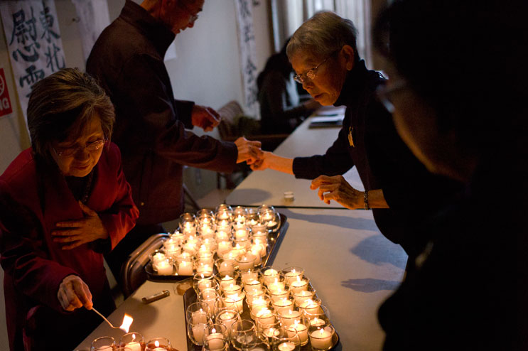 Worshippers and temple workers light candles during a memorial service for the victims of the March 2011 earthquake and tsunami in Japan at Zenshuji Soto Mission in Little Tokyo in Los Angeles, Calif., Sunday, March 20, 2011.