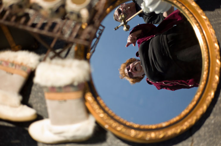 Visitors of the Rose Bowl Flea Market are reflected in a mirror displayed by a vendor at the Rose Bowl Flea Market in Pasadena, Calif., Sunday, April 10, 2011.