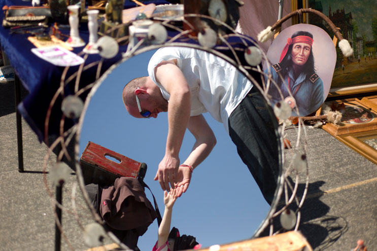 Dean Stockton, of London, England, is reflected in a mirror displayed by a vendor as he plays with his four-year-old daughter Olivia at the Rose Bowl Flea Market in Pasadena, Calif., Sunday, April 10, 2011. The Stocktons heard about the flea market back in England and decided to include it in their trip to Los Angeles. ''We planned the market around our trip,'' Dean Stockton said.