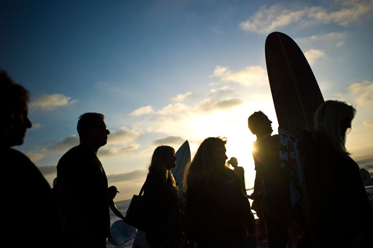 "People gather at the San Clemente beach after a paddle-out memorial for Jeff ""Ox"" Kargola, a young motocross driver who died last April, May 11, 2011."