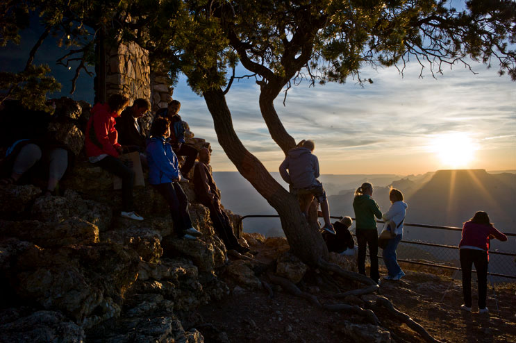 Park visitors gather at the Desert View Watchtower to watch the sunset over Grand Canyon National Park, Arizona, Thursday, June 2, 2011.
