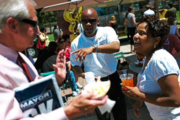 2011 mayoral candidate Michael Hancock, center, introduces his twin sister Michelle Hancock, right, to his friend Larry Fullerton at the Civic Center EATS Outdoor Cafe in Denver, Colo., Tuesday, June 7, 2011.