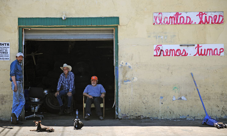 "From left, Valentine Diaz, Tony Arevalo and Angel Acosta wait for customers with Acosta's chihuahuas Mia, left, and Chata at his tire shop ""Del Llano Tire & Wheel"" on Santa Fe Drive Tuesday, June 14, 2011."
