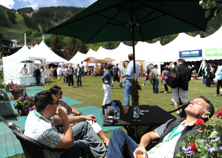 "Howard Greenstone, right, the CEO of New York City-based Rosa Mexicano, relaxes with his employees Jason Berry and Grace Hu in the courtyard of the Grand Tasting Pavilion at the Food & Wine Classic in Aspen Saturday morning, June 18, 2011. ""This is hangover position,"" he said. ""I'm sweating out some of last night's champagne."""