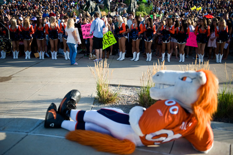 Denver Broncos mascot Miles watches as cheerleaders fire up a crowd of potential contesters in front of Invesco Field at Mile High before the American Idol Season 11 auditions in Denver, Friday, July 29, 2011.