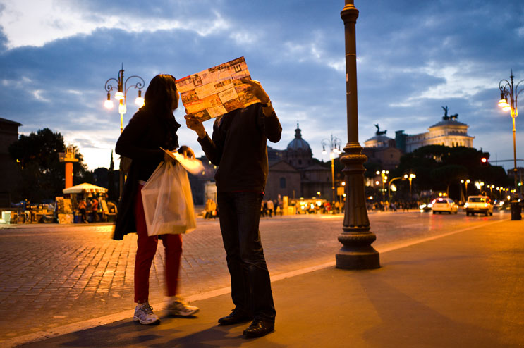 Tourists study a map at the Via dei Fori Imperiali near the Colosseum in Rome, Italy, Monday, October 31, 2011.