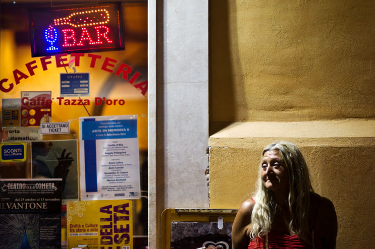 A woman stands next to a café near the Foro Piscario in Rome, Italy, Monday, October 31, 2011.
