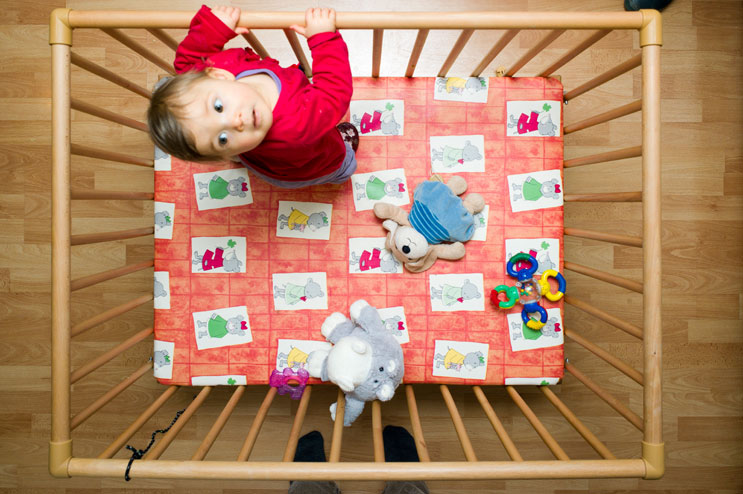Nine-month-old Clara explores the world above her crib, Saturday, March 3, 2012.