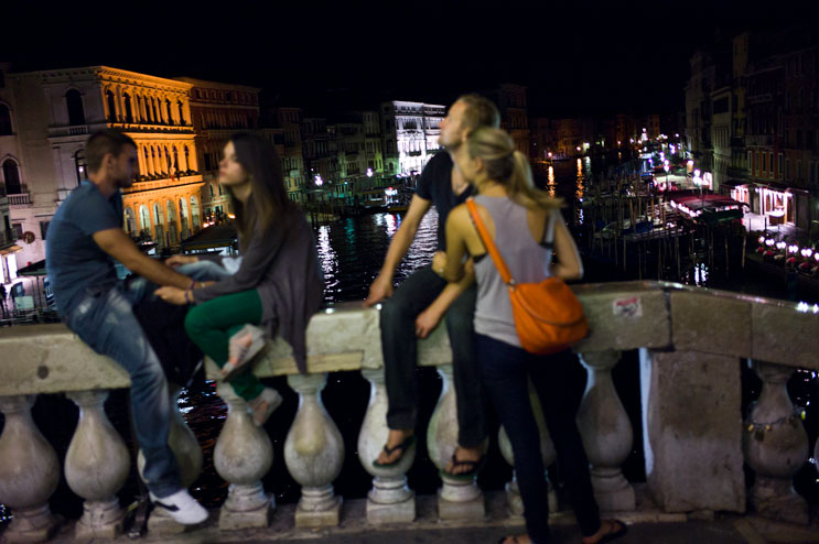 Two young couples hang out on the Rialto Bridge across the Grand Canal in Venice, Italy, Wednesday, June 27, 2012.