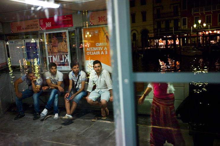 A group of young men watches a girl pass by at the Rialto vaporetto station in Venice, Italy, Wednesday, June 27, 2012.