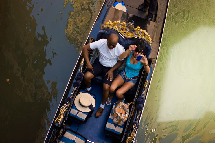 A tourist couple enjoys a Gondola ride in the Cannaregio neighborhood in Venice, Italy, Wednesday, June 27, 2012. Formerly the only means of transportation in Venice, there are now about 500 gondolas left. At € 80.00 for a 40-minute ride during the day and € 100.00 at night, a gondola ride is an expensive affair.