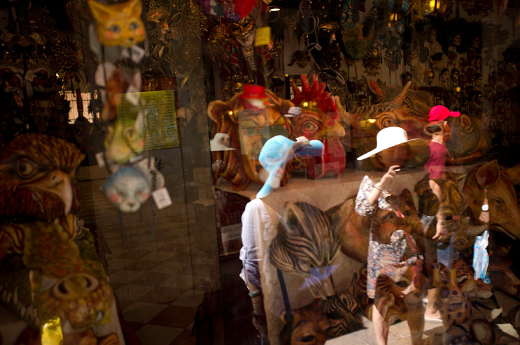 Tourists snap a picture of carnival masks displayed in a store window in the San Marco quarter in Venice, Italy, Wednesday, June 27, 2012. Genuine Venetian masks are handmade and very costly. Unsuspecting tourists often fall for the cheaper and low-quality imitations from East Asia sold by street vendors and in souvenir shops.