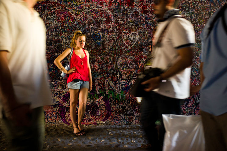 A girl strikes a pose for her friend's camera in the passage leading into the courtyard of the Casa di Giulietta (Juliet's house) in Verona, Italy, Saturday, June 30, 2012.