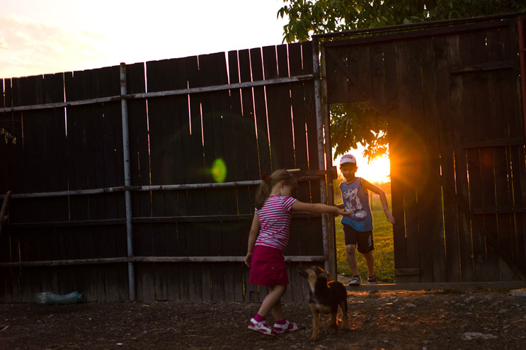 Calin's niece and and nephew, Raluca and Rares, play with the family dog in the chicken coop of Calin's house in Targu Mures. Tuesday, July 10, 2012.