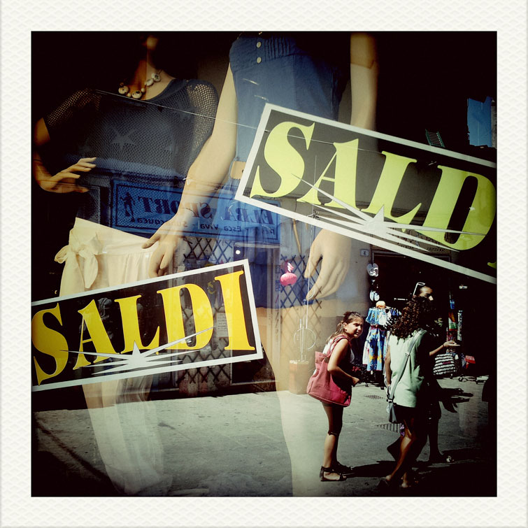Pedestrians pass by a store window on Via Calamita in Capoliveri on the Tuscan Island of Elba, Italy, Thursday, August 8, 2012.