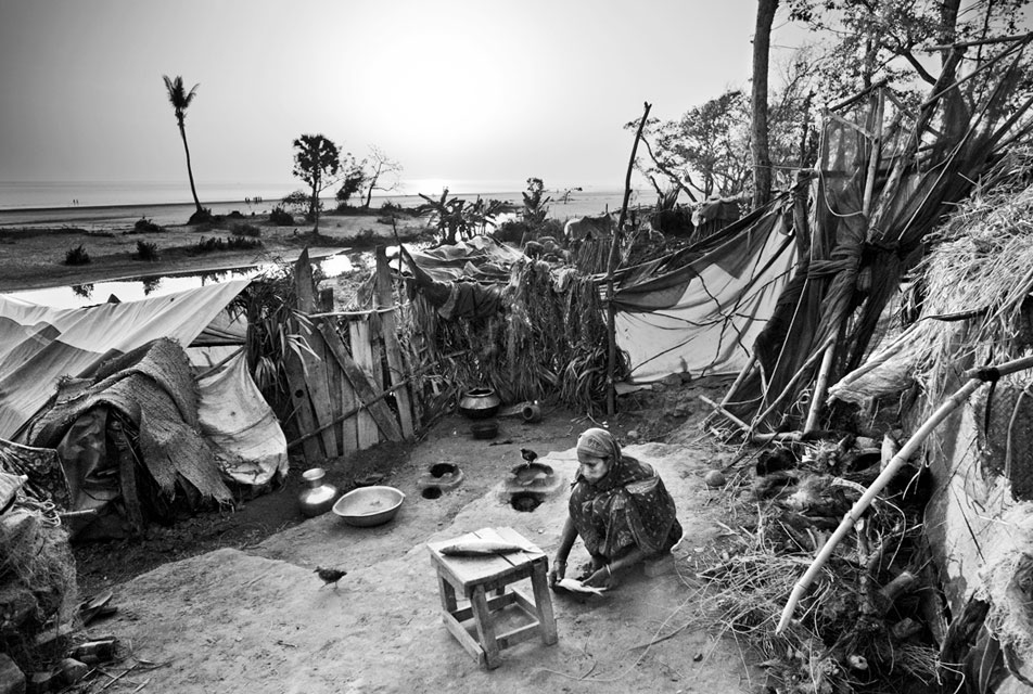 Amid a cluster of makeshift huts, a woman prepares fish for dinner. When tropical cyclone Sidr hit the coast of Bangladesh on the night of November 15, 2007, it forced thousands of people into makeshift huts constructed from whatever the storm left them. Kuakata, Bangladesh, Feb. 22, 2008.